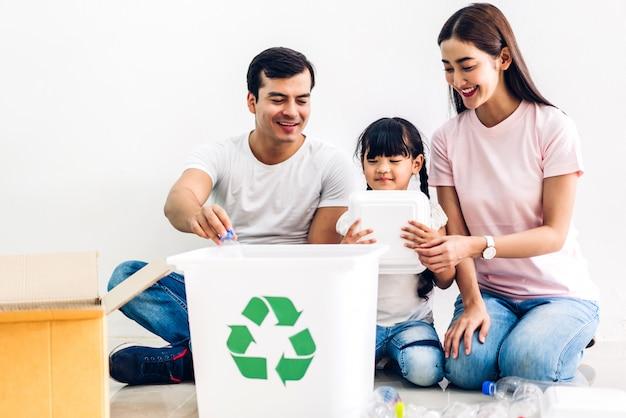 空のリサイクルペットボトルと紙をリサイクルボックスに入れて楽しんで幸せな笑顔の家族