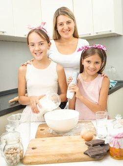 Happy smiling family making dough for pie on kitchen