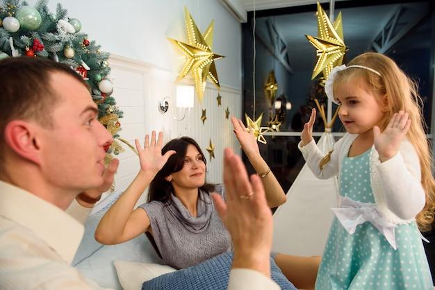 크리스마스 배경 근처에 행복 웃는 가족이 서로 놀아요.