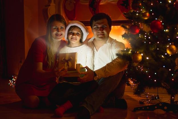 벽난로에 앉아 크리스마스 선물 상자를 여는 행복한 웃는 가족