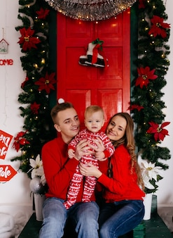 Happy smiling family at studio on background of the christmas tree with gift