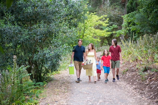 Happy smiling family walking in park. mother, father and children with picnic basket having walk in park or forest. holding hands