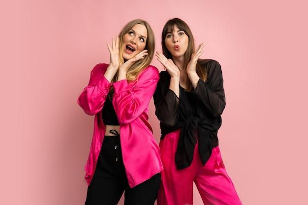 Счастливые улыбающиеся модные девушки в стильной красочной одежде, позирующие на розовой стене