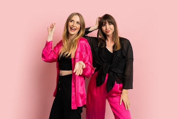 Happy smiling fashionable girls wearing stylish colorful outfit, posing on pink wall