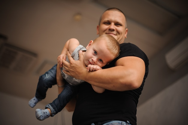 Happy smiling father holding a son in his hands