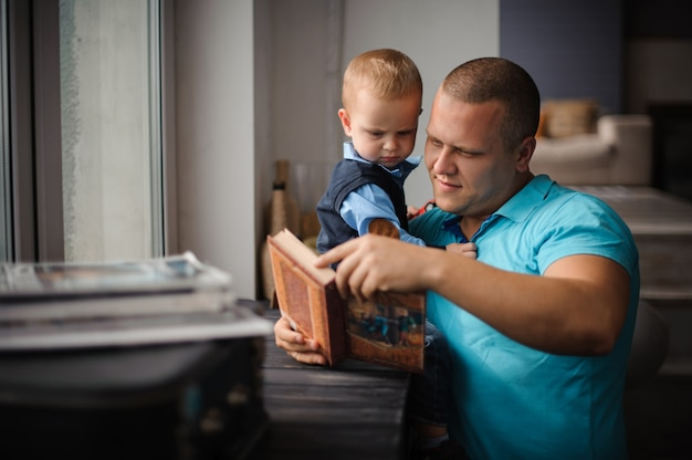 Happy smiling father and little son reading book
