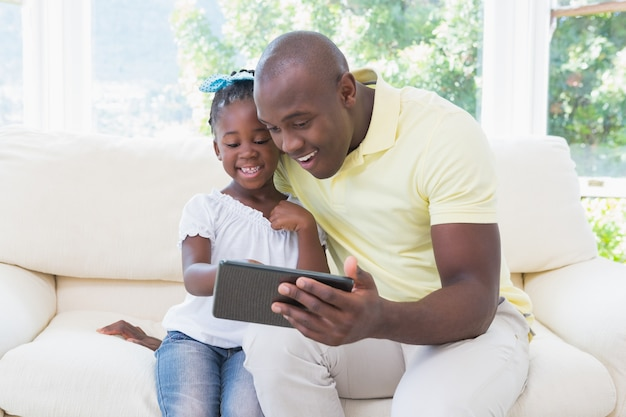 Счастливый улыбающийся отец, используя цифровой планшет с дочерью на диване