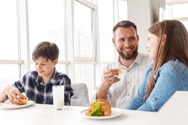 Счастливый улыбающийся отец с детьми 8-10, завтракают вместе на светлой кухне дома и едят бутерброды с круассанами