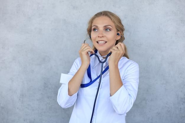 灰色の背景に分離された白い制服のコートと聴診器で幸せな笑顔の女性医師。