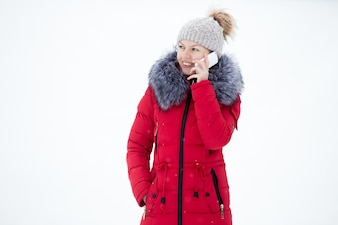 Happy smiling female in red winter jacket talks on mobile phone, outdoors, against the snow