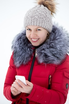 Happy smiling female in red winter jacket texting with mobile phone, outdoors against the snow, looks in camera