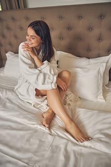 침대에서 시간을 보내는 흰색 부드러운 목욕 가운에 행복 웃는 여성