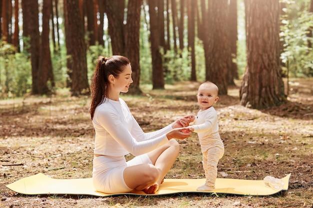 Счастливая улыбающаяся женщина в белой модной спортивной одежде сидит на спортивном коврике на открытом воздухе и держит детские ладони