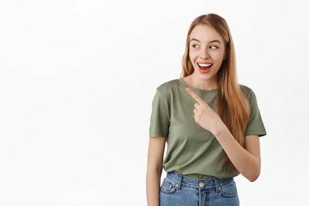 Modello femminile sorridente felice che indica, guardando a sinistra e ridendo su un banner, mostrando qualcosa di divertente da parte, in piedi in maglietta contro il muro bianco