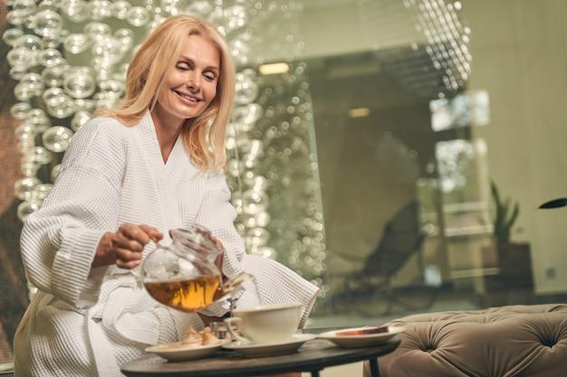 유리 책상에 앉아있는 동안 컵에 차를 붓는 행복 웃는 여성