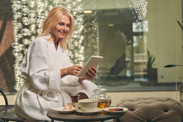 테이블에 차와 주전자의 컵에 휴식을 취하는 동안 태블릿을 사용하여 행복 웃는 여성