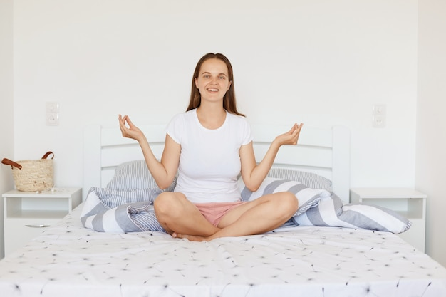 Happy smiling female wearing white casual style t shirt and shorts, sitting on bed in light bedroom, meditating at home in morning, expressing positive emotions.
