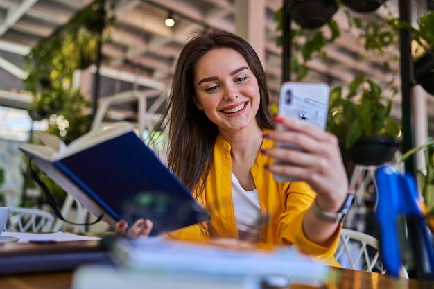 Счастливый улыбающийся женский работник, выступая по видеовызову в офисе с мобильным телефоном.