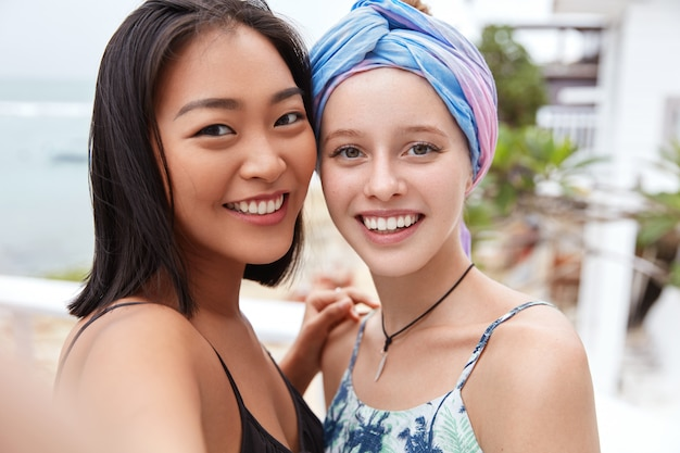 Happy smiling females with joyful expressions, have different nationalities and positive looks.