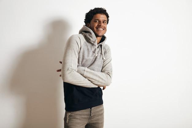 Счастливый улыбающийся темнокожий парень носит пустой серый черный свитер с капюшоном и рваные джинсы, скрестив руки на груди, изолированные на белом
