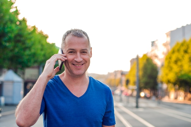 Happy smiling forty years old caucasian tourist man talking on a mobile phone outdoor.