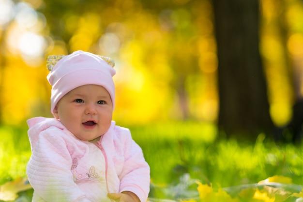 コピースペースとクローズアップの肖像画で秋の森の草の上に座って幸せな笑顔フレンドリーな若い女の赤ちゃん