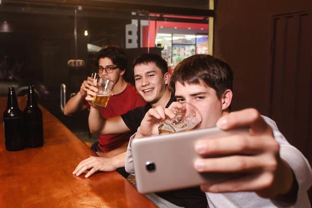 Счастливые улыбающиеся друзья, делающие селфи, попивая пиво в баре.