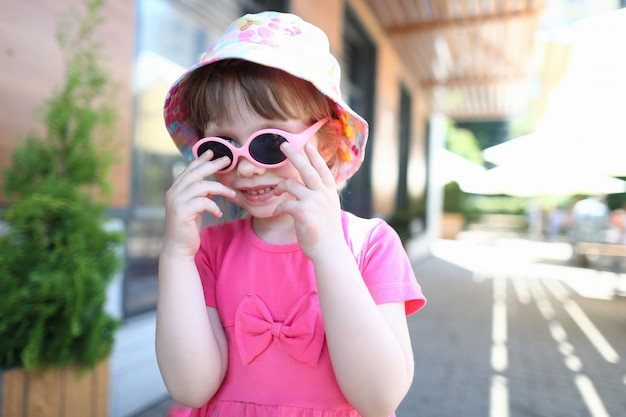 Happy smiling girl child in sunglasses outdoor portrait