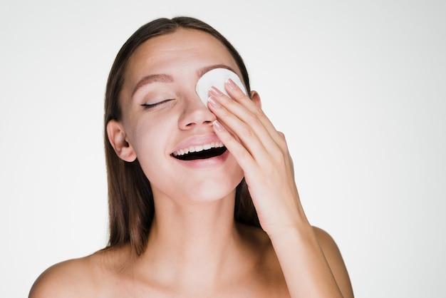 행복한 웃는 소녀는 면봉으로 피부를 정화한다