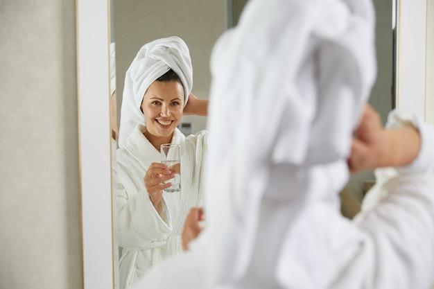 浴室の女の子の鏡の前に立っている水のガラスを飲んで保持している幸せな笑顔の女の子