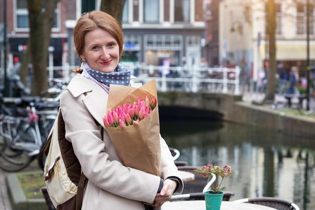 Счастливая улыбающаяся девочка, держащая букет тюльпанов, стоящая на улице амстердама. нидерланды