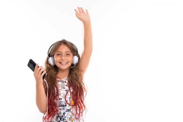 Счастливая улыбающаяся девушка держит руку и слушает музыку в наушниках