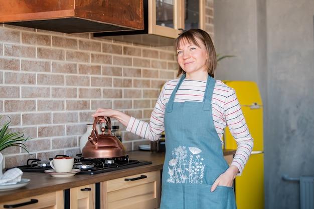 エプロンで幸せな笑顔の女の子は、やかんとストーブのそばのキッチンに立っています