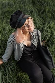 Счастливая улыбающаяся девушка в модной винтажной одежде с шляпой и черной сумкой, сидя на зеленой траве на закате
