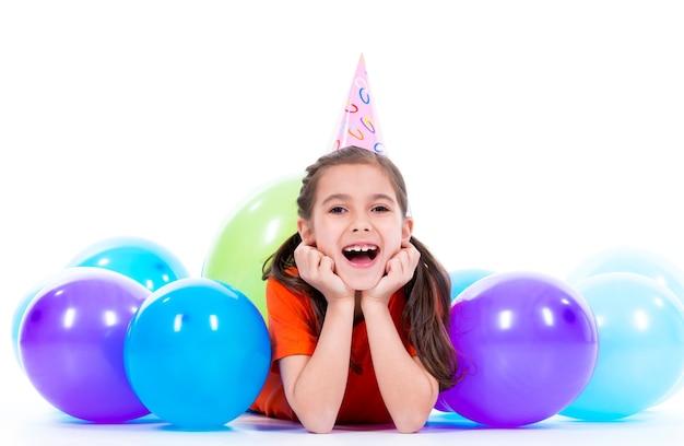 カラフルな風船と床に横たわっているオレンジ色のtシャツの幸せな笑顔の女の子-白で隔離