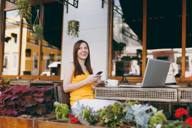 ラップトップpcコンピューター、携帯電話の友人にテキストメッセージメッセージ、自由時間中にレストランでテーブルに座って屋外通りのコーヒーショップカフェで幸せな笑顔の女の子
