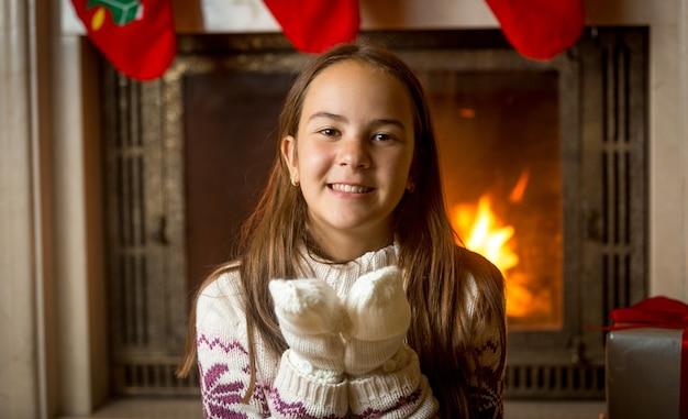 燃える暖炉と飾られたクリスマスツリーでポーズをとってセーターと手袋で幸せな笑顔の女の子