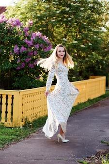 幸せな笑顔の女の子が田舎道で踊っています。彼女はロングドレスを着ています。