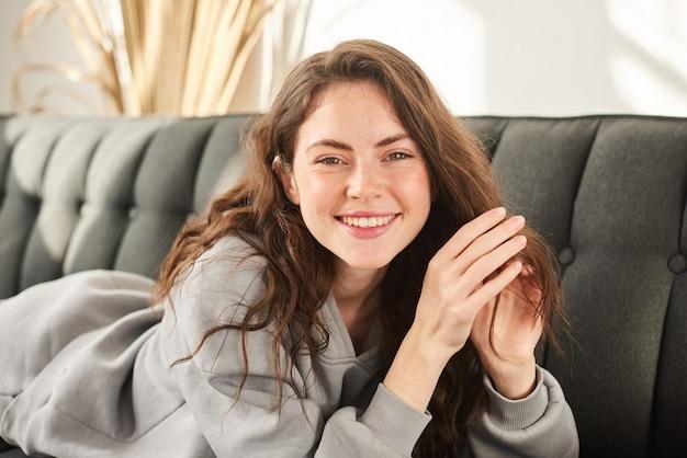 Счастливая улыбающаяся девушка лежит на диване