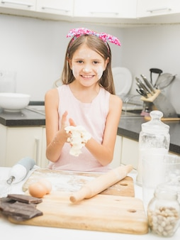 부엌에 파이 반죽을 만드는 행복 한 웃는 소녀