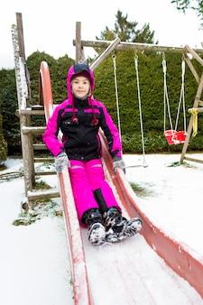 Счастливая улыбающаяся девушка на горке в холодный снежный день