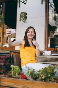 Ragazza sorridente felice in caffè di strada all'aperto caffè seduto al tavolo con computer pc portatile facendo prendendo selfie shot sul telefono cellulare nel ristorante durante il tempo libero