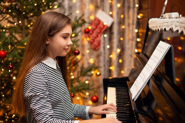Happy smiling girl playing the piano with bright decorations on the background