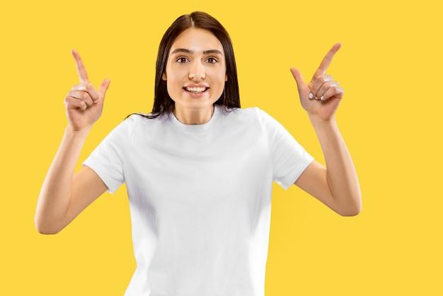 幸せな笑顔の女の子が上向き。黄色の壁に分離された美しい女性の半分の長さの肖像画。若い笑顔の女性。ネガティブスペース。顔の表情、人間の感情の概念。