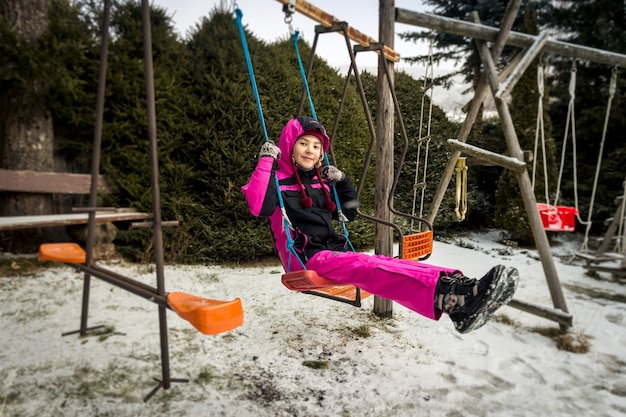 Счастливая улыбающаяся девушка катается на качелях на детской площадке в снежный день