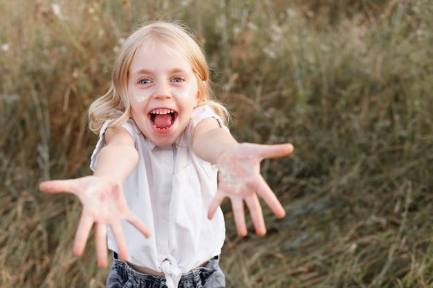 幸せな笑顔の女の子は夏の背景に彼女の手を示しています