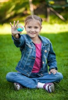 잔디에 앉아 지구 공을 손에 들고 행복 웃는 소녀 프리미엄 사진
