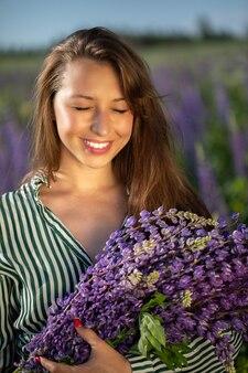 一握りの野花と日光に目を細める幸せな笑顔の女の子