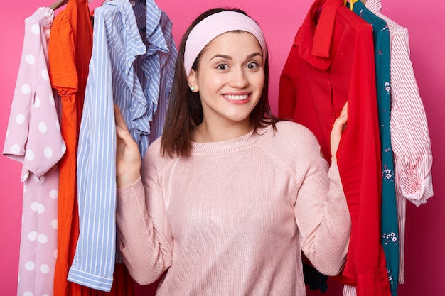 Happy smiling girl stands between hangers with blouses in fashion store. cheerful woman visits boutique. cute lady likes to go to mall. beautiful young female on sale. shopping and fashion concept.