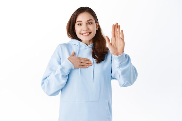 행복한 미소 짓는 여학생은 손을 들고 가슴을 만지고, 자원하고, 몸짓을 하고, 자신에 대해 이야기하고, 흰 벽에 서서